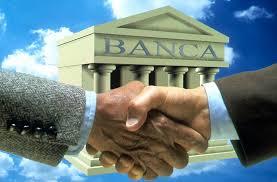 due mani che si stringono davanti a un modellino di banca